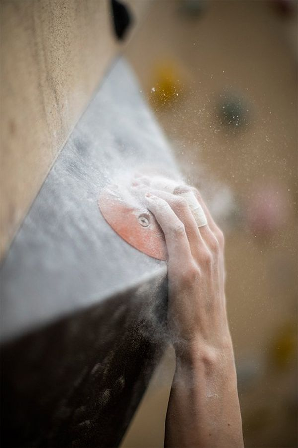 A close-up of an athlete's hand, powder-covered fingertips clinging to a hold in a climbing wall.