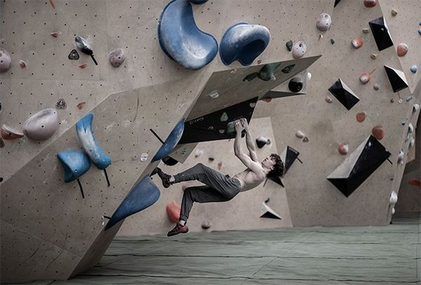 A male athlete hangs almost horizontal under a climbing wall, one leg in the air.