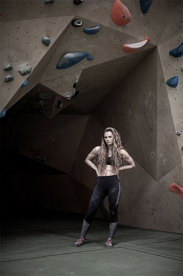 A female climber stands, hands on hips, under a climbing wall with colourful handholds.