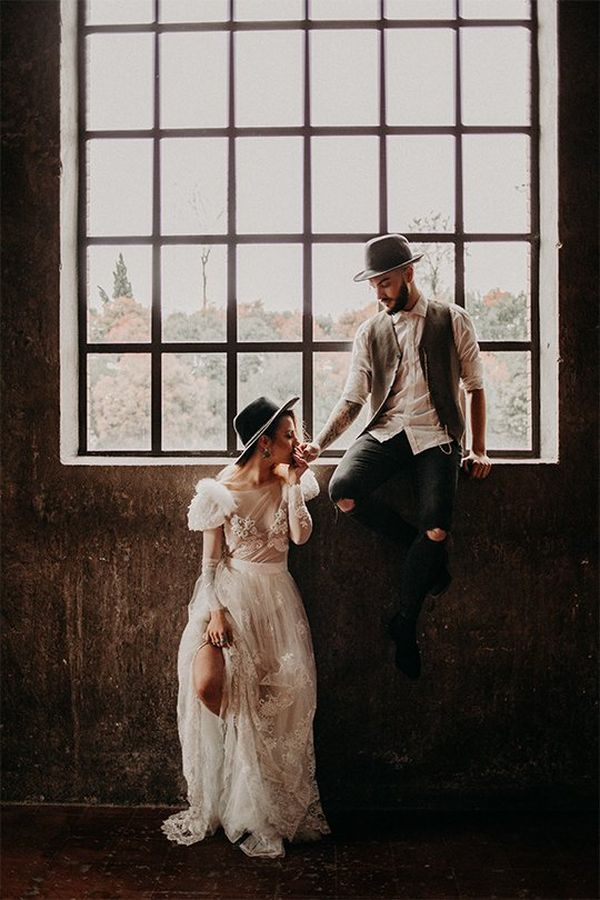 Bride poses against wall while the groom sits on the window ledge. Photo by Factoria182.