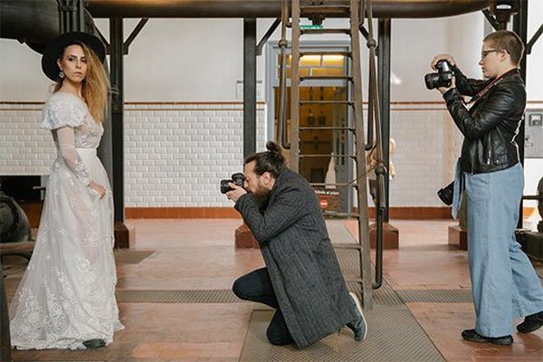 Two photographers point their Canon cameras at a bride to take her portrait.