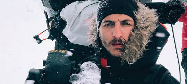 Cinematographer Giacomo Frittelli, wearing a dark hooded parka, holds a video camera in the snow.