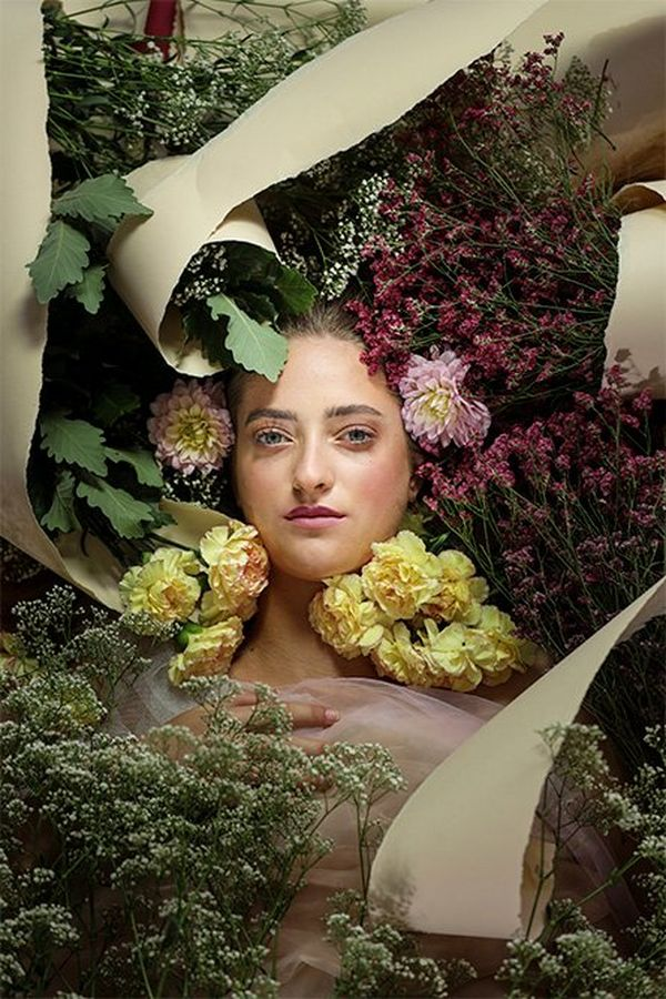 A white model's face appears among flowers as she lies on the floor with twists of torn paper also arranged around her.