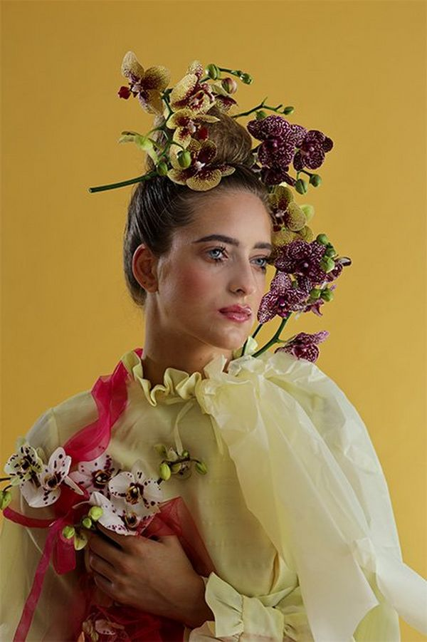 A white model has orchids and fabric draped over and around her, against an ochre backdrop in a studio portrait with a yellow theme.