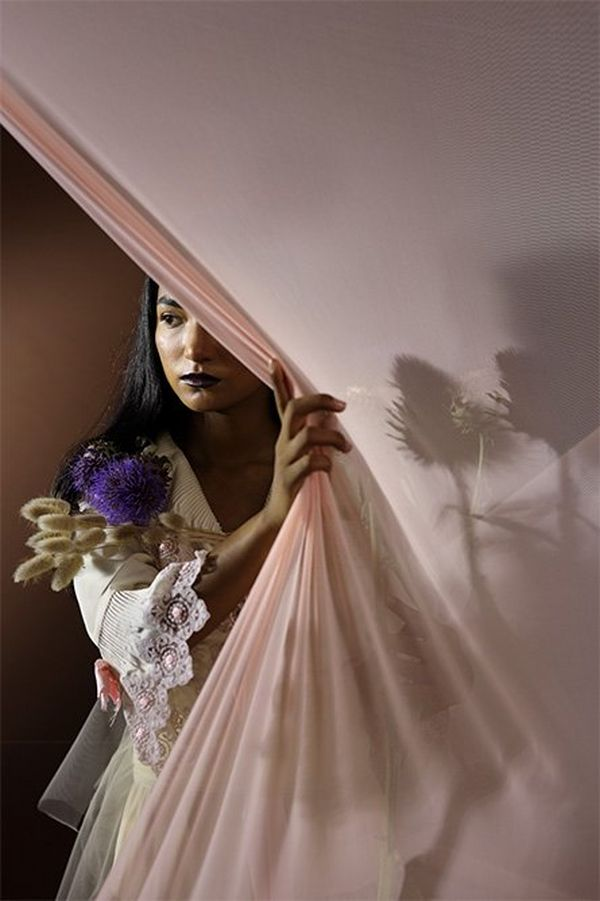 An Indian model pulls a light pink partition to the side, revealing herself standing behind.