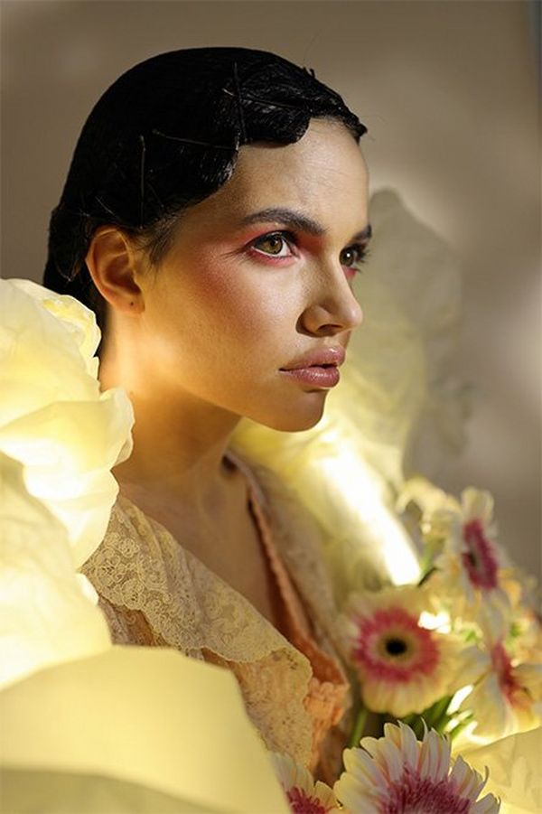 A luminous ring hangs around a white models' neck, who's holding flowers and looking pensively into the distance.