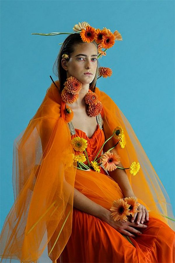 A striking sitting portrait of a white model with intense orange fabric and flowers arranged over her, against a cyan backdrop.