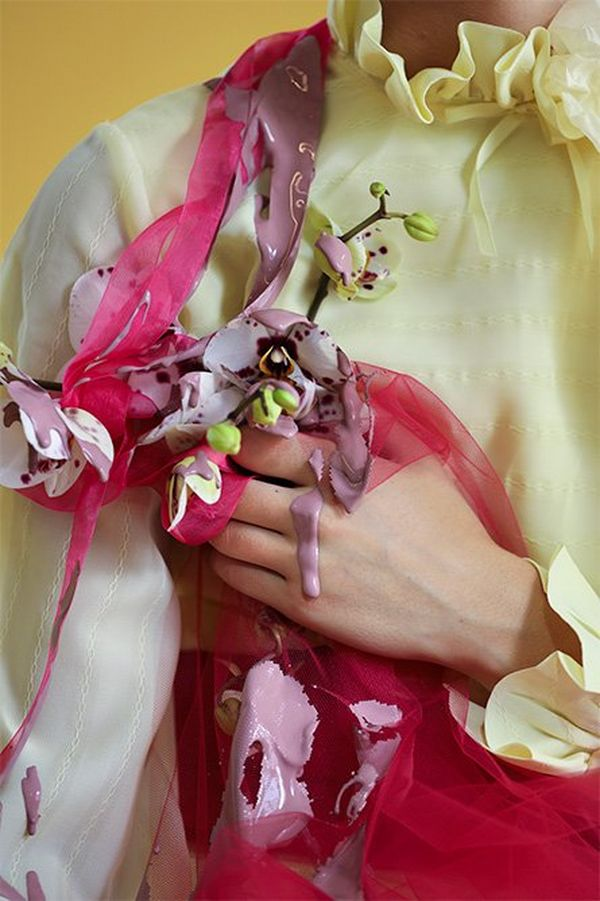 A close-up photograph of a white model's hand holding orchids, fabric and with paint dripping off her shoulder and hand.