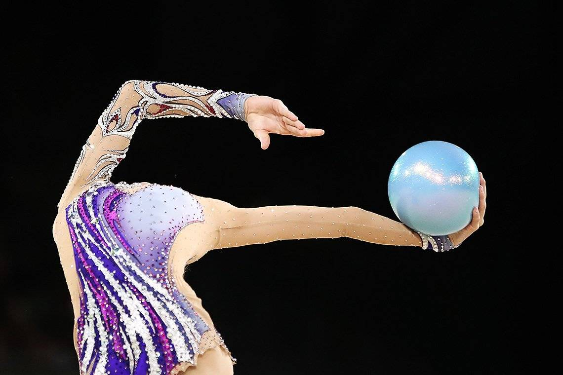 A gymnast holding a ball appearing headless
