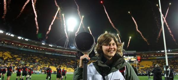 Photographer Hannah Peters holds a Canon camera as she stands in a rugby stadium, fireworks in the background.