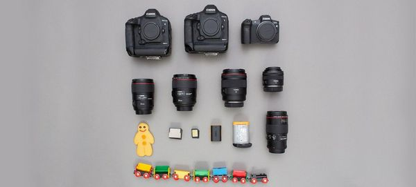 Two Canon EOS-1D X Mark II camera bodies, a Canon EOS R body, and various lenses, batteries and memory cards, plus a child's toy train and gingerbread man.