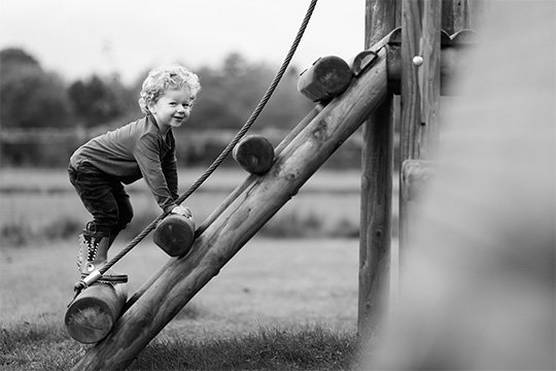 A black-and-white shot of a little boy at the park climbing a wooden climbing frame. Photo by Helen Bartlett.