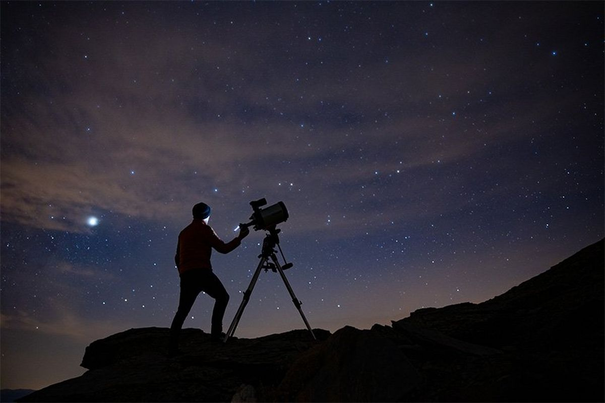Silhouetted against the night sky, an astrophotographer stands on steep terrain with a Canon EOS Ra attached to a telescope.
