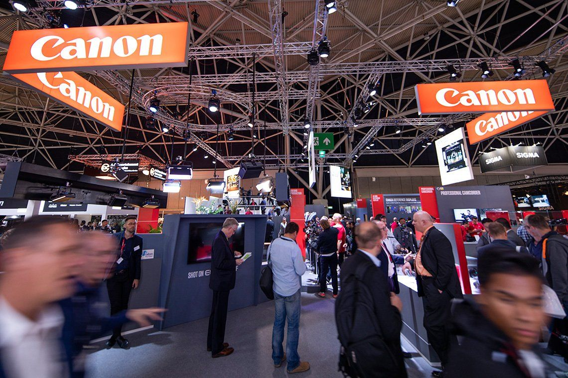 Visitors at Canon's IBC 2018 stand try out pro video cameras.