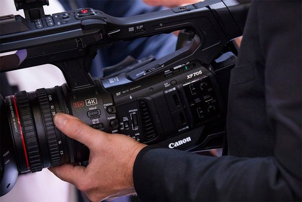 A man's hands hold a Canon XF705 video camera.