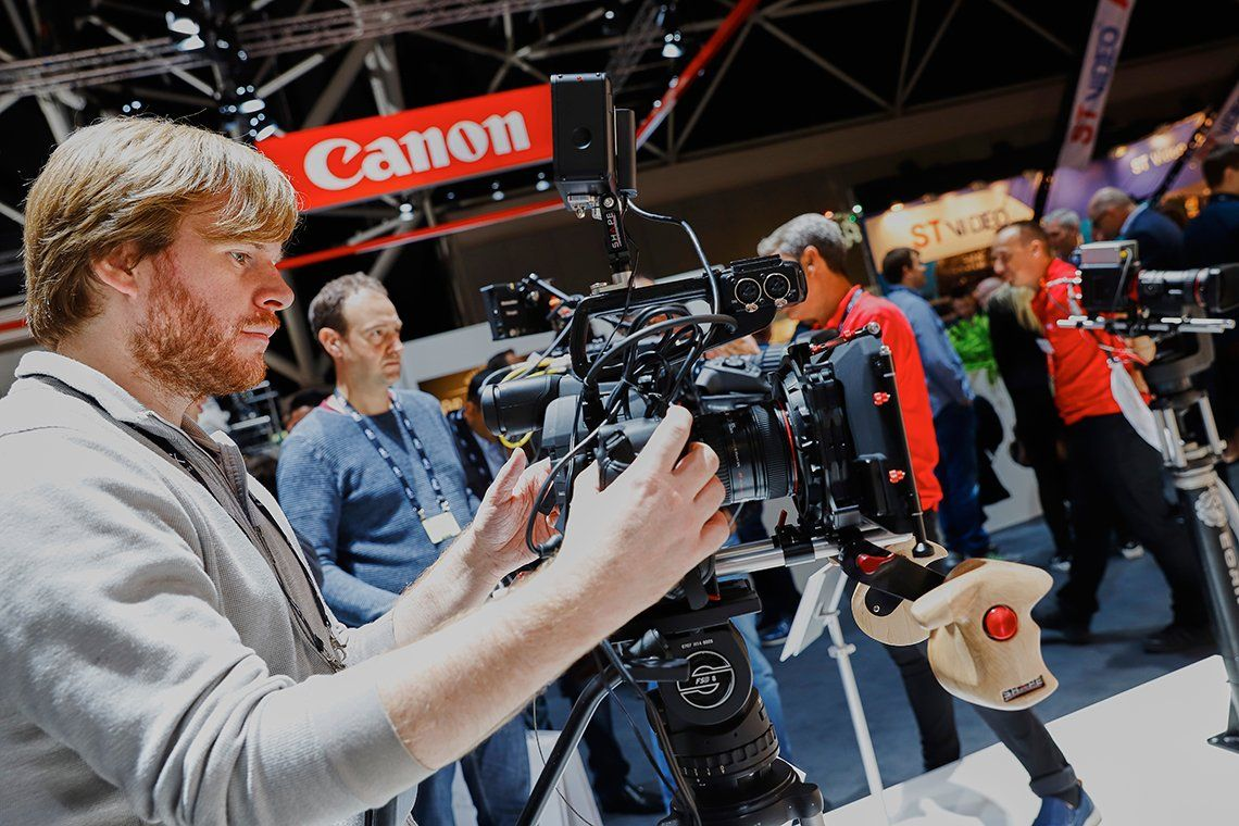 A man operates a Canon video camera on the Canon stand at IBC 2017.