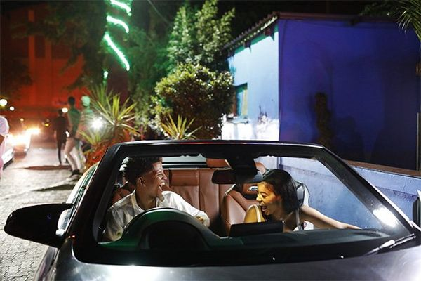 An affluent young couple in an expensive open-top car.
