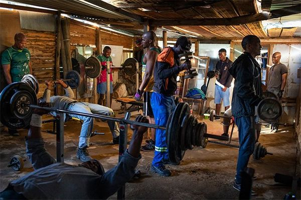 Men working out in a makeshift gym.