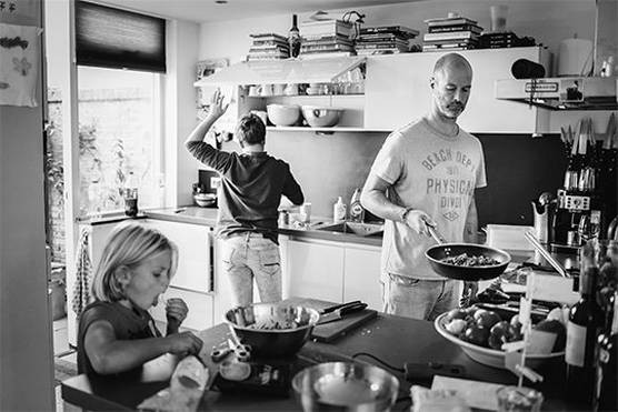 A man wearing t-shirt and jeans, frying pan in hand, prepares a meal in a bright kitchen. A teenage boy reaches up to a cupboard in the background, while an 8-year-old girl eats something in the foreground.