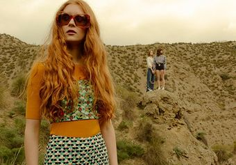 A female model stands outside in the foreground, with two other female models standing on a hill in the background.