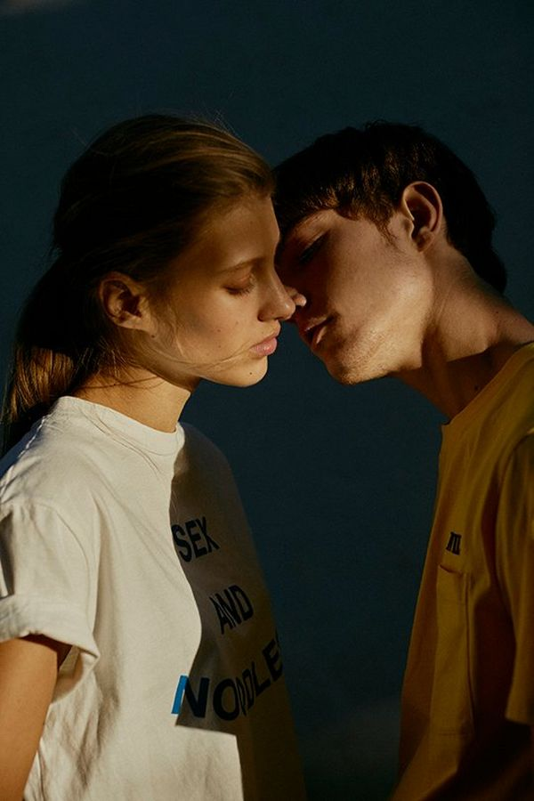 Two young models are poised to kiss, a shadow cast in between them.
