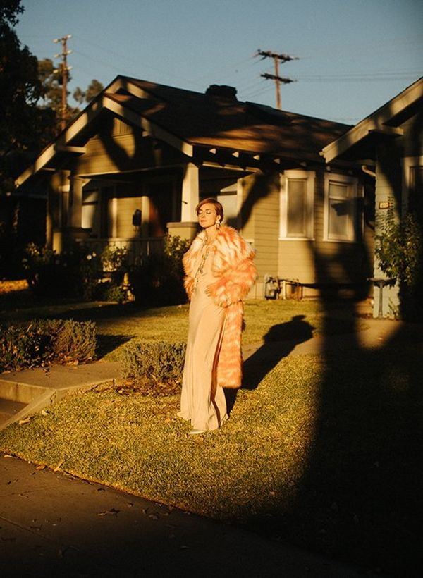 A woman stands in the front garden of a single-storey clapboard house, casting a long shadow as she faces a sunset.