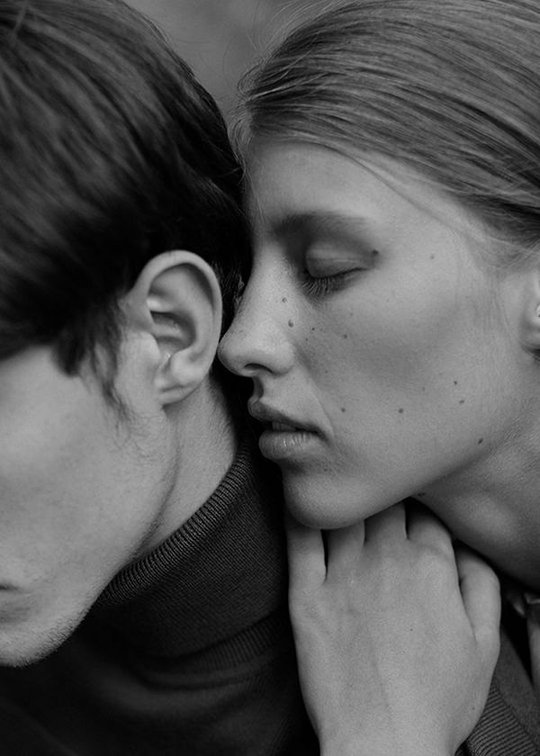 A black and white shot is composed with a young man mostly out of frame, his jaw and ear in shot, as a woman leans close to whisper to him.