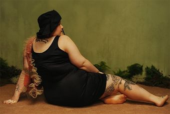 Plus-size, tattooed model Ami is photographed from behind, sitting with her legs to one side in a pose reminiscent of Old Master paintings of reclining models.