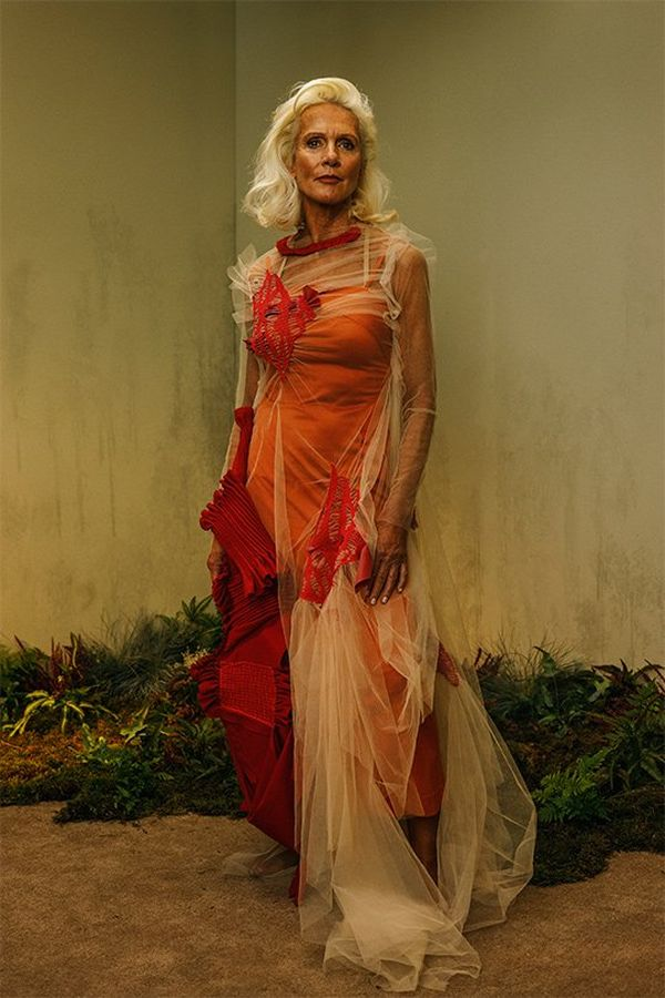 A silver-haired older woman stands tall and elegant, in a figure-hugging orange dress swathed with lace around the shoulders and tumbling to the floor on one side and concertina swags of red fabric on the other side.