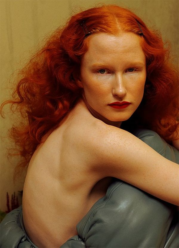 Red-haired model Maisie looks straight at the camera over her bare shoulder.