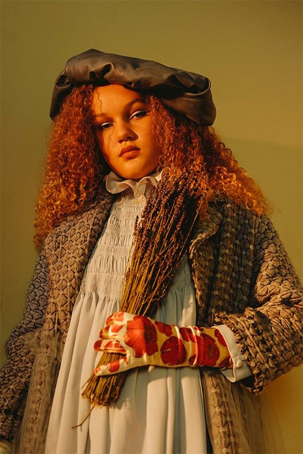 A woman with tightly curled red hair, wearing a rustic-looking smock, coat, hat and red flowery glove, looking slightly down at us, holding a sheaf of dried lavender.