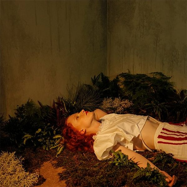 A redheaded woman wearing a silky off-white blouse and red and white striped trousers lies on her back on a bed of greenery with the corner of the set visible behind.