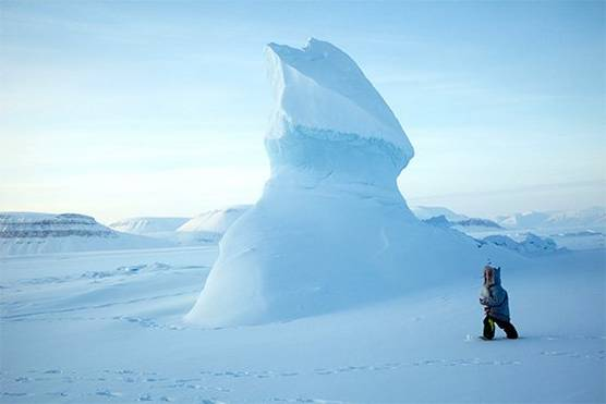 A man walking in the bleak Arctic landscape.