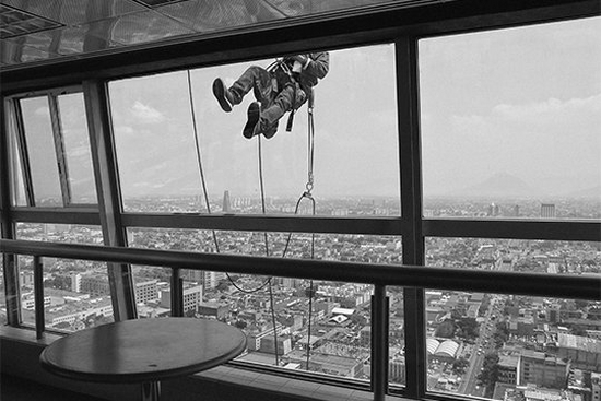 A window cleaner outside the 40th floor of the Torre Latinoamericana in Mexico City, with the sprawling city below. Photograph by Jérôme Sessini.
