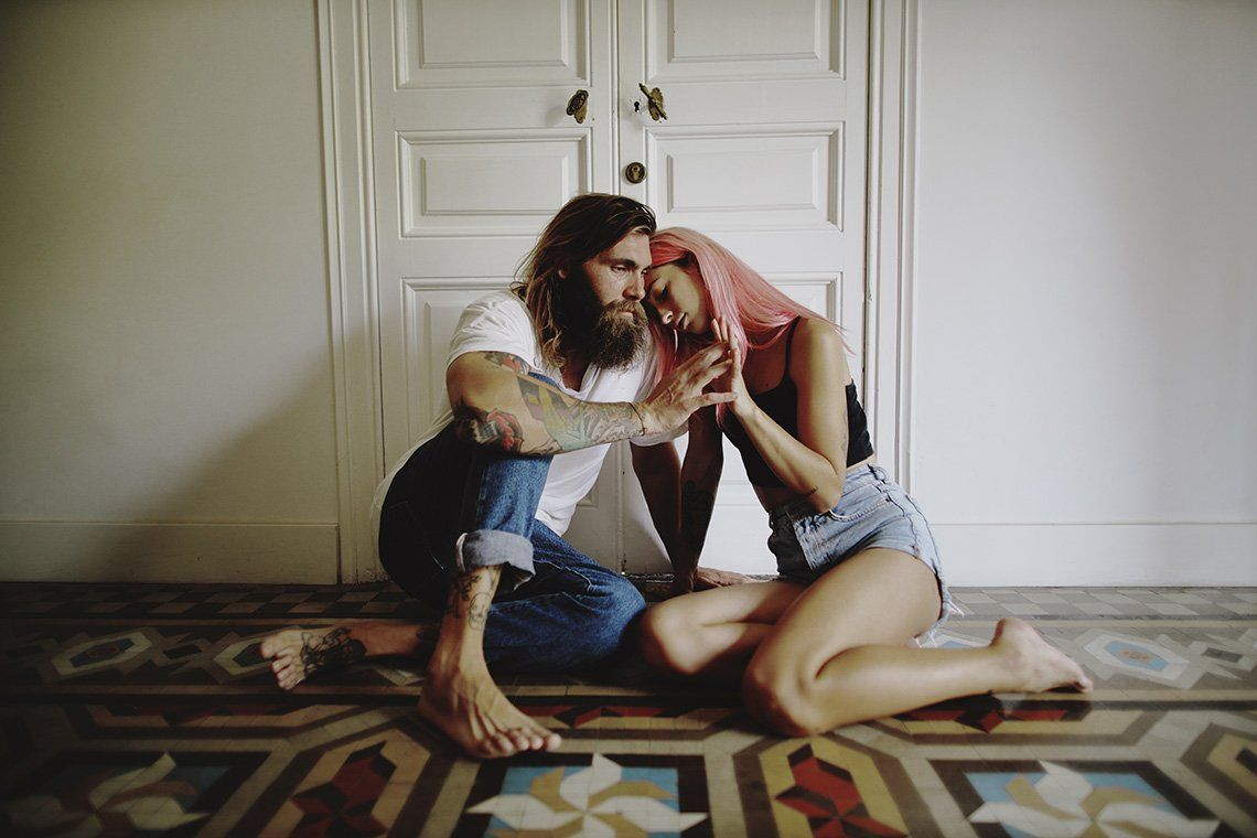 A long-haired, bearded man and a pink-haired woman sit on a tiled floor, their fingers intertwined.