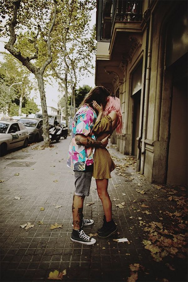 The couple kiss under the trees on a deserted street in Barcelona.