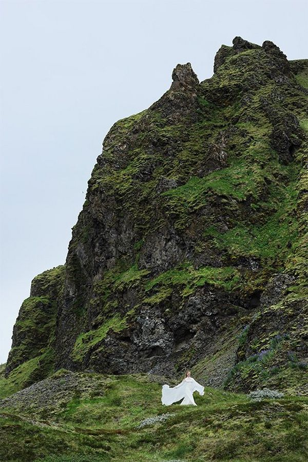 A woman in a flowing white wedding dress stands at the base of a steep, grassy rock face.