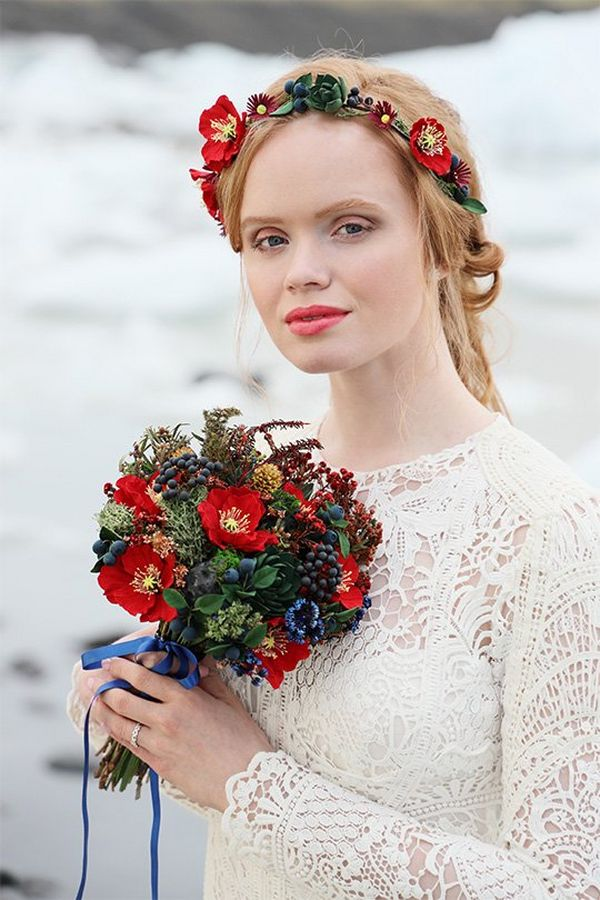 A strawberry blonde woman in a white lace wedding dress and flower headband holds a small bouquet of mixed red and blue flowers against an out-of-focus background of ice.