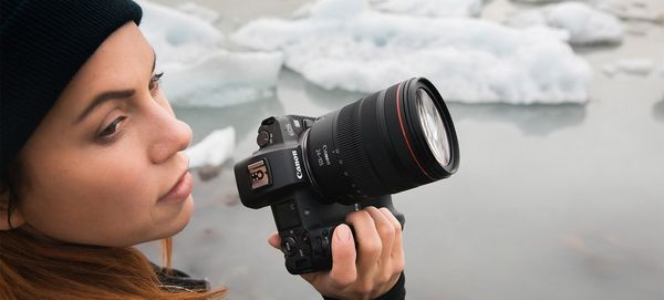 Photographer Katya Mukhina stands in front of a body of water with icebergs in it, holding a Canon EOS R in her right hand.