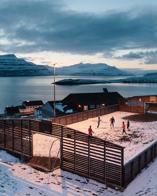 Five youngsters play football in a snow-covered ground inside a wooden fence; the waters of a chilly fjord are visible in the background.