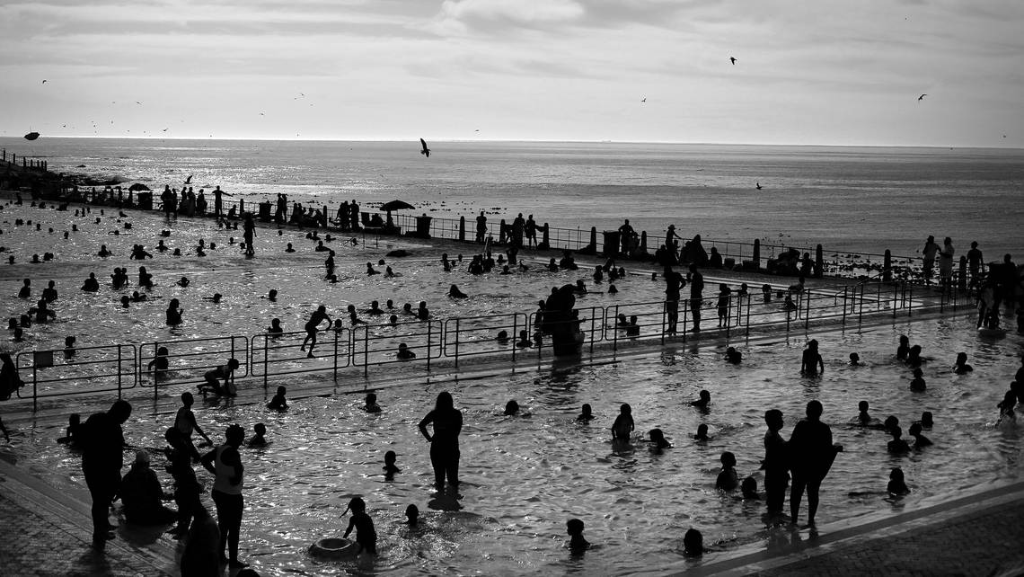 A black-and-white image from Kim Ludbrook's Contre-Jour retrospective of bathers in silhouette at Sea Point swimming pool in Cape Town, South Africa.
