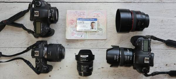 The contents of Kim Ludbrrok's kitbag – three Canon cameras and 4 lenses – laid out on a table.
