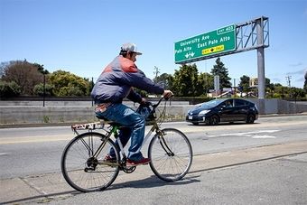A cyclist and a car travel under a highway sign indicating the exit for University Avenue, Palo Alto and East Palo Alto. Photo by Laura Morton.
