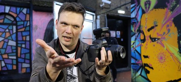 Photographer James Musselwhite holds a camera as he gestures to someone we can't see, in front of some street art.