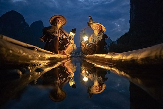 Two elderly Chinese cormorant fishermen sit in their boats in near darkness. One has a cormorant sitting on his shoulder. Taken by Joel Santos on a Canon EOS 5D Mark IV.