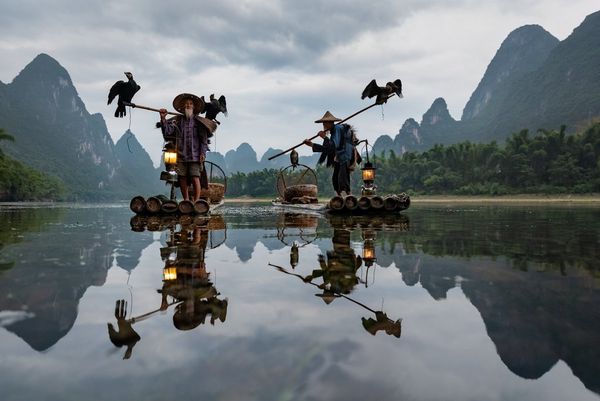 Two fishermen stand on their boats, each with a staff over his shoulder. A cormorant perches at the end of one staff and both ends of the other. The entire scene is reflected in the still water.