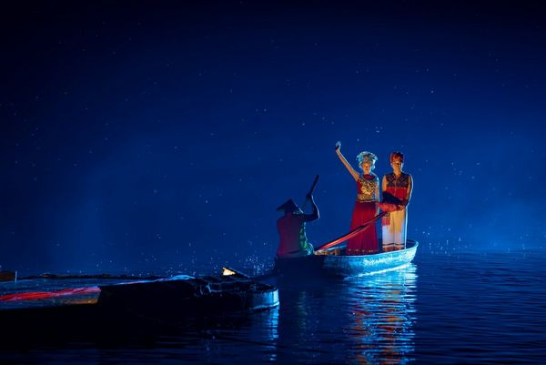 At night, a man and a woman stand on a boat in the River Li. The woman's arm is raised. Taken by Joel Santos on a Canon EOS 5D Mark IV.