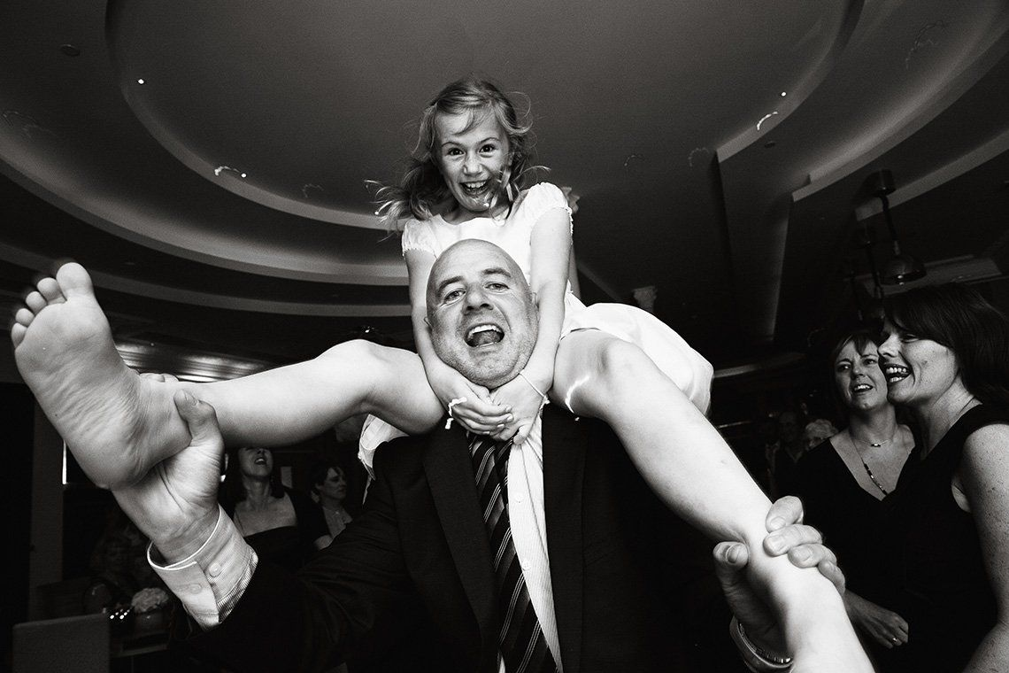 A man dances with his daughter on his shoulders, both laughing and looking at the camera.