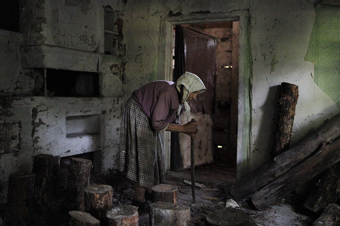 A hunched woman in a derelict house in Chernobyl.