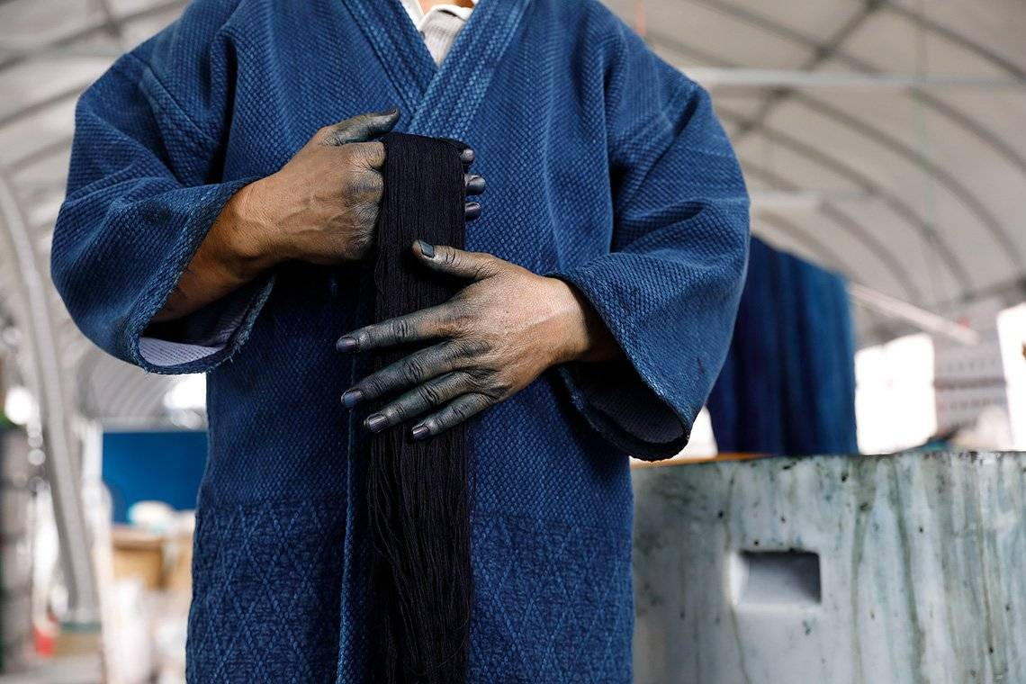 In a film still from Made in Japan, a denim factory worker holds a piece of fabric with indigo-stained hands.